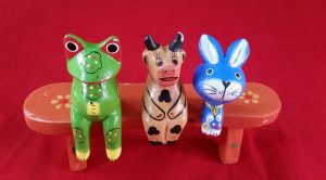 Cute, wooden figures (Frog, Cow, Rabbit) on bench